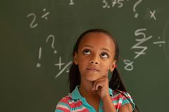 Schoolgirl standing against green board in a classroom at school. Front view of a thoughtful mixed-race schoolgirl standing against green board in a classroom at royalty free stock photos
