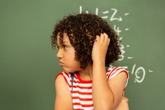 Schoolgirl standing against green board in a classroom at school. Front view of a thoughtful mixed-race schoolgirl holding her head and standing against the stock photos