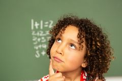Schoolgirl standing against green board in a classroom at school. Portrait of a cute thoughtful mixed-race schoolgirl standing against green board in a classroom royalty free stock photo