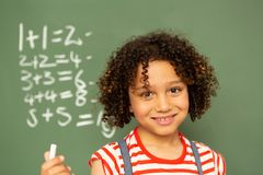 Schoolgirl standing against green board in a classroom at school. Portrait of a mixed-race schoolgirl standing against green board and holding a chalk in a stock image