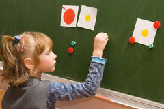 The schoolgirl standing at a blackboard. At the lesson in the classroom Stock Photography