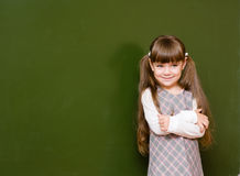 Schoolgirl standing in class near a green blackboard Royalty Free Stock Photos