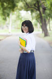 Schoolgirl standing holding a book. Stock Images