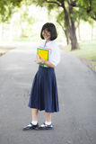 Schoolgirl standing holding a book. Stock Photos