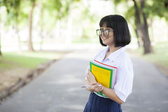 Schoolgirl standing holding a book. Stock Photography