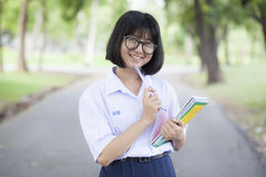 Schoolgirl standing holding a book. Royalty Free Stock Images