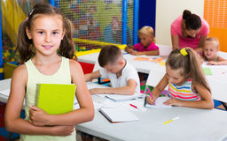 Schoolgirl standing with textbook in elementary class Royalty Free Stock Image