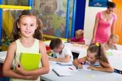 Schoolgirl standing with textbook in school class. Cheerful schoolgirl standing with textbook in elementary school class indoors Stock Photo