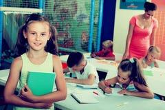Schoolgirl standing with textbook in school class. Cheerful schoolgirl standing with textbook in elementary school class indoors Stock Images