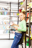 Schoolgirl stands and holds books in library Stock Images