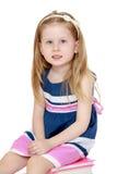 Schoolgirl in striped dress Stock Images