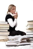 Schoolgirl or student kisses teddy-bear. Around her lie books. Isolated on white Royalty Free Stock Images