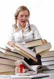 Schoolgirl or student and rolling-over books. She has glasses on her nose. There is a mess but she is satisfied, since she is ended to teach. On white Royalty Free Stock Photo