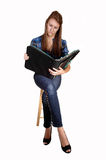 Schoolgirl studying. A pretty teenager sitting on a chair, in jeans and a blue chickened blouse with a notebook in her hand, for white background royalty free stock photography