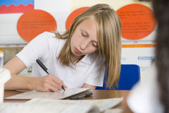 A schoolgirl studying in class Stock Photo