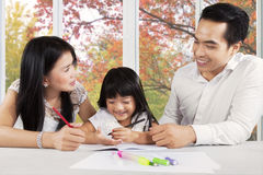Schoolgirl studying with her parents Royalty Free Stock Photos