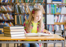 Schoolgirl studying in the library Royalty Free Stock Photo