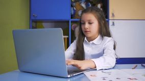 SchoolGirl Studying at the Library Doing after lessons Homework with laptop PC. Elementary school with devices. Child. Cute little girl studying at the library stock video
