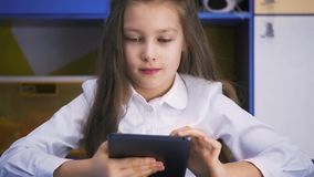 SchoolGirl Studying at the Library Doing after lessons Homework with tablet PC. Elementary school. Child reading. Cute little girl studying at the library and stock video footage
