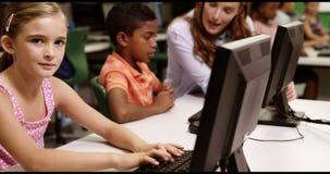 Schoolgirl studying on personal computer in classroom. At school stock video
