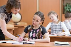 Schoolgirl is studying. School kids work at lesson. Teacher controlling learning process. stock image