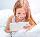 Schoolgirl with tablet in bed at Royalty Free Stock Images