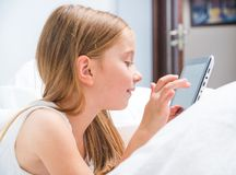 Schoolgirl with tablet in bed at Royalty Free Stock Image