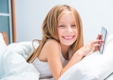 Schoolgirl with tablet in bed at Royalty Free Stock Photos