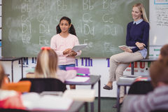Schoolgirl taking lesson of her classmates Royalty Free Stock Images