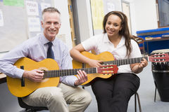 Schoolgirl and teacher playing guitar stock photo