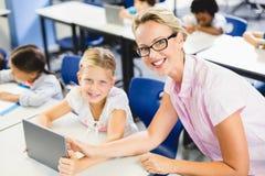 Schoolgirl and teacher using digital tablet in classroom. At school Stock Images