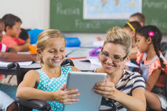 Schoolgirl and teacher using digital tablet in classroom. Smiling schoolgirl and teacher using digital tablet in classroom at school Royalty Free Stock Photo