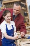 Schoolgirl and teacher in woodwork class Royalty Free Stock Photos