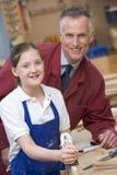 Schoolgirl and teacher in woodwork class Stock Photo