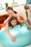 Schoolgirl teasing friend on gym ball Royalty Free Stock Photo