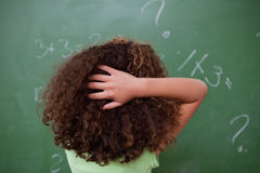Schoolgirl thinking about algebra while scratching the back of h Royalty Free Stock Image