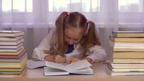 Schoolgirl thinking and doing her homework at table with books. Schoolgirl thinking and learning lessons. Cute girl doing her homework. Adorable schoolchild stock footage