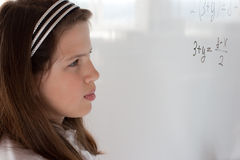 Schoolgirl is thinking on equation solution Stock Photos