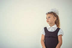 Schoolgirl thinking in uniform, funny face Royalty Free Stock Photography