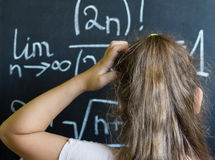 Schoolgirl thinks on the difficult task of mathematics stock photography