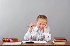 Schoolgirl thinks over the difficult task Royalty Free Stock Photography