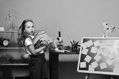Schoolgirl with tired face. Girl carries pile of books to desk with microscope stock images