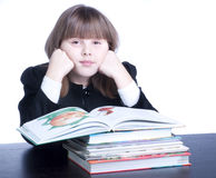 Schoolgirl. Tired and sad schoolgirl in black uniform sitting at a table in front of her stack of books she reads Stock Photos