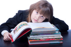 Schoolgirl. Tired and sad schoolgirl in black uniform sitting at a table in front of her stack of books she reads Royalty Free Stock Photo