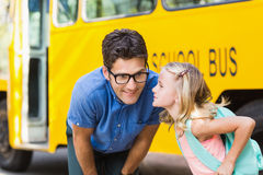 Schoolgirl about to kiss a teacher in front of school bus Stock Photo