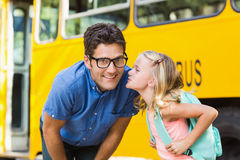 Schoolgirl about to kiss a teacher in front of school bus Stock Photography