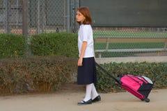 Schoolgirl with trolley bag. Girl dragging school trolley bag Stock Photo
