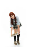 Schoolgirl trying to lift a heavy stack of books Royalty Free Stock Photography