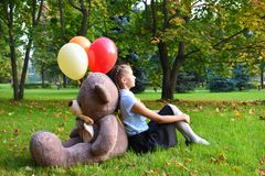 Sad  girl with big teddy bear and balloons in the park.  Problems teenagers at school