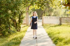 Schoolgirl in uniform with a backpack and books goes to school stock image